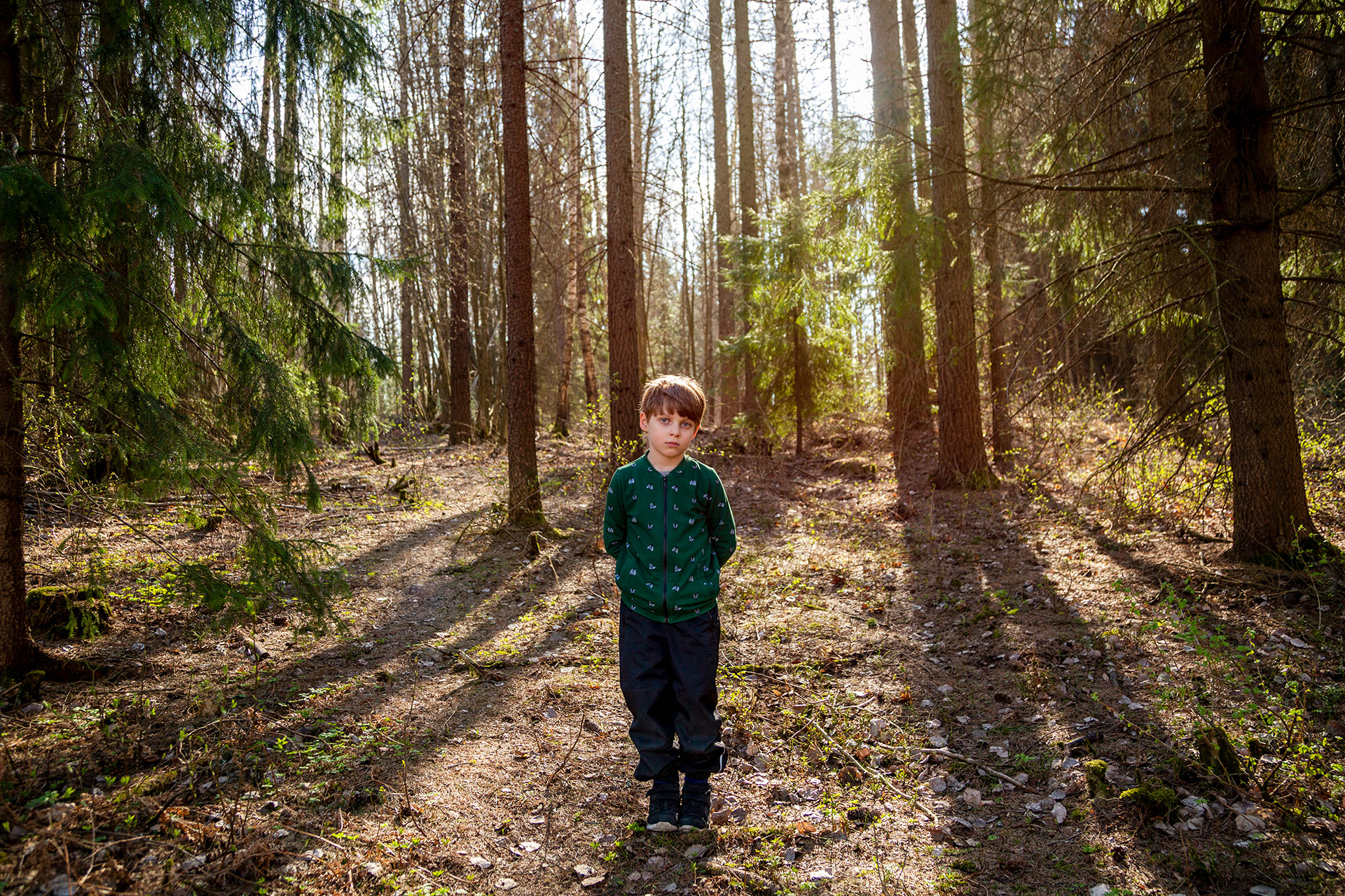 Portrait of a boy standing in a forrest